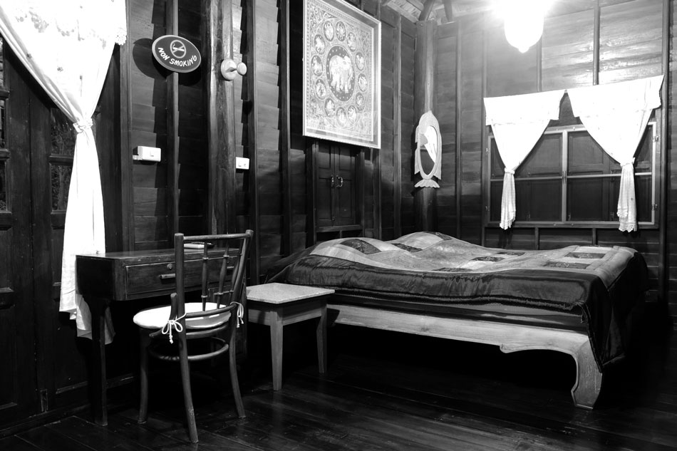 ห้องนอนเรียบง่ายด้วยการวางที่นอนนุ่มหนาไว้บนเตียงไม้ มีโต๊ะเก้าอี้โบราณเป็นที่ทำงาน บรรยากาอุ่นๆ ช่วยให้หลับสบายโดยเฉพาะในช่วงในเพิ่งขาดสาย