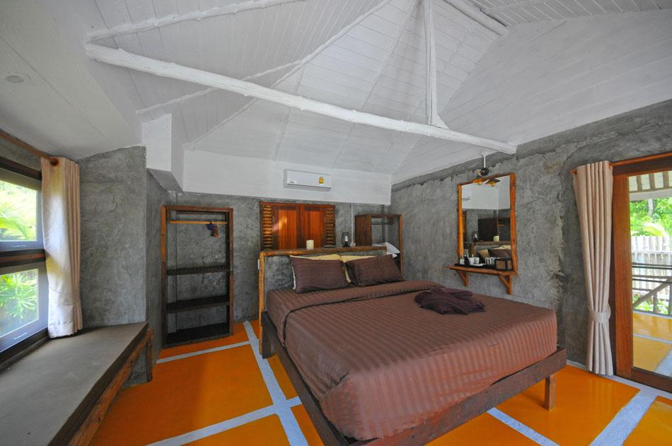 ห้องนอนกว้าง มีพื้นที่ต่อเนื่องจากครัวและบาร์ ด้านซ้ายทำเป็นที่นั่งขนานไปกับผนัง ด้านหลัง (หลังหัวนอน) มีประตูเปิดออกไปหาห้องน้ำ โดยรวมดูดิบเดิม ไม่เพิ่มอะไรให้รกเรื้อ เป็นงานออกแบบเรียบง่าย สบายๆ แต่ดูด็  | Tan Marina Bay