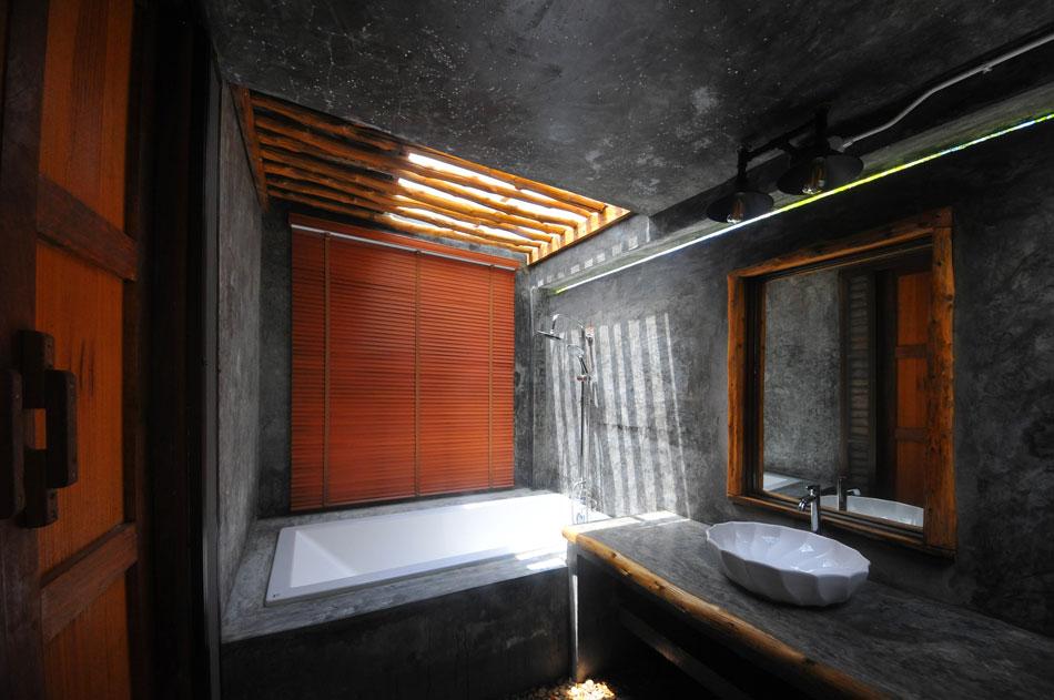 ห้องน้ำส่วนนี้มีอ่างอาบน้ำอยู่ด้านในสุด หลังคาปล่อยให้แสงสาดลงมาทำให้ห้องน้ำแบบปูนเปลือยไม่ทึบตัน เพิ่มความรู้สึกผ่อนคลายมากขึ้น  | Tan Marina Bay