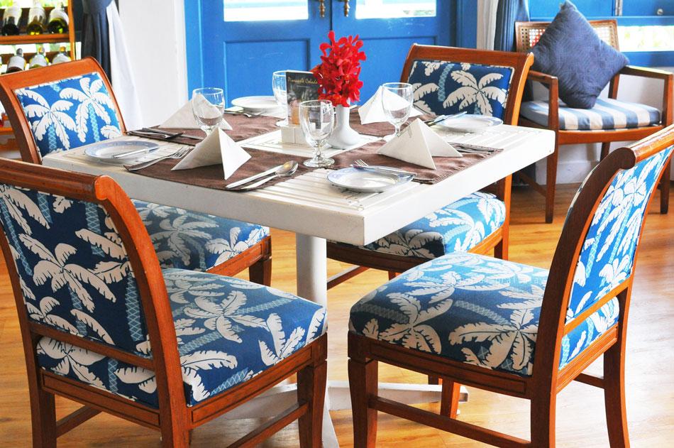 เก้าอี้ไม้บุนวมหนาหุ้มด้วยผ้าลายมะพร้าวสีฟ้าสดใสให้อารมณ์ทะเลชัดเจน