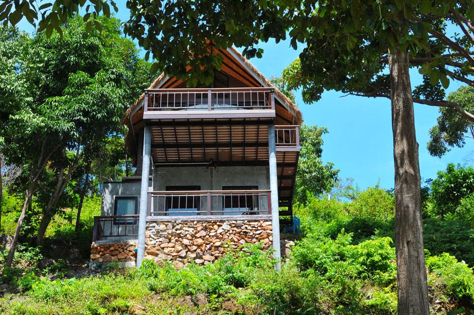 บ้านสองชั้นปลูกสร้างบริเวณเชิงเขา ลักษณะเป็นบ้านคันทรีประยุกต์ ใช้วัสดุผสมผสานระหว่างปูนเปลือย หินภูเขา ไม้ เป็นบ้านหลังใหญ่ รองรับครอบครัวขนาดใหญ่ได้สบาย  | Tan Marina Bay